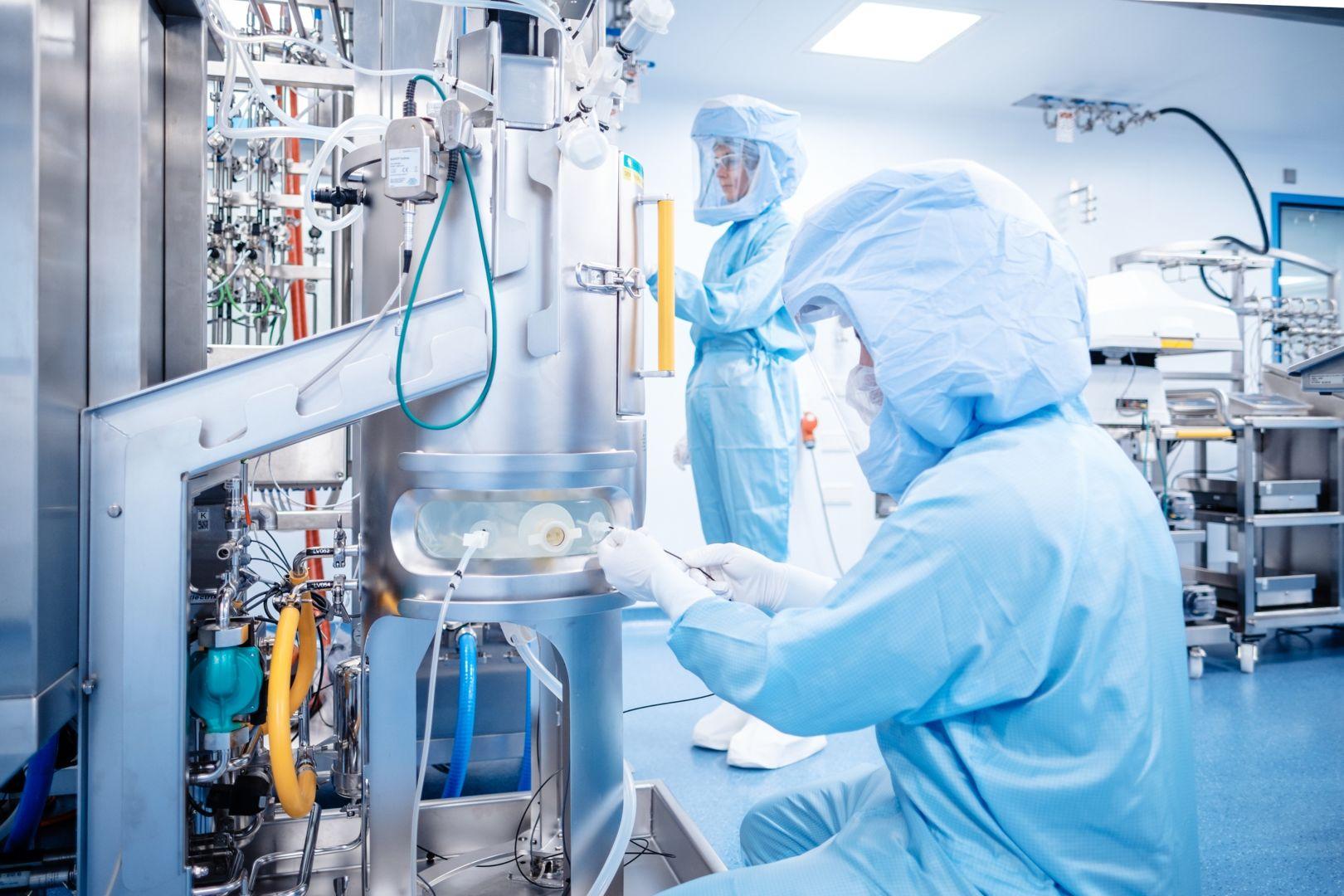 Forscher mit Schutzanzug arbeiten in einem Labor für die BioNTech-Impfstoffherstellung.