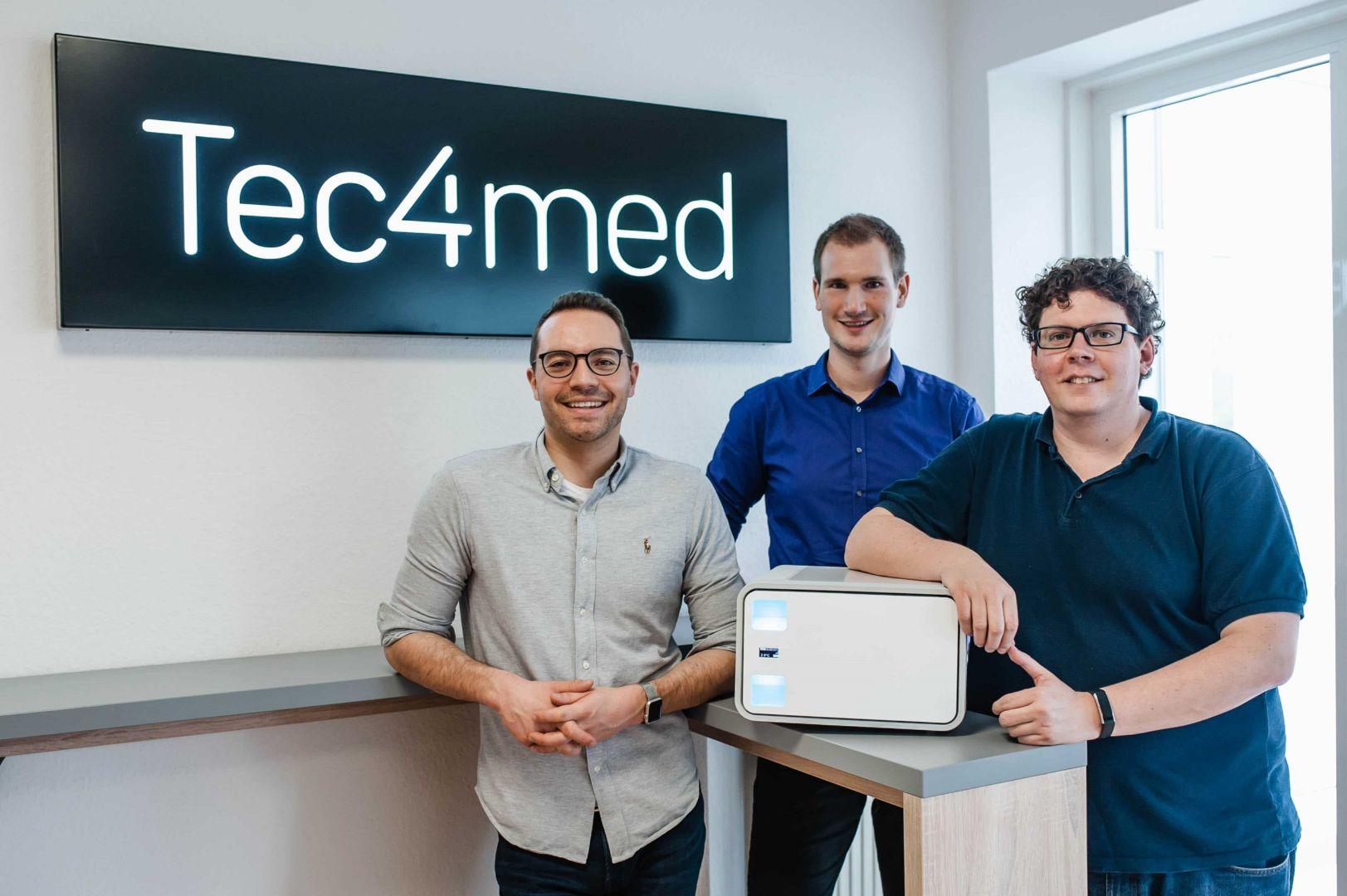 Drei Mitarbeiter von Tec4med stehen mit einer Kühlbox für Spezialtransporte vor dem Firmenschild.
