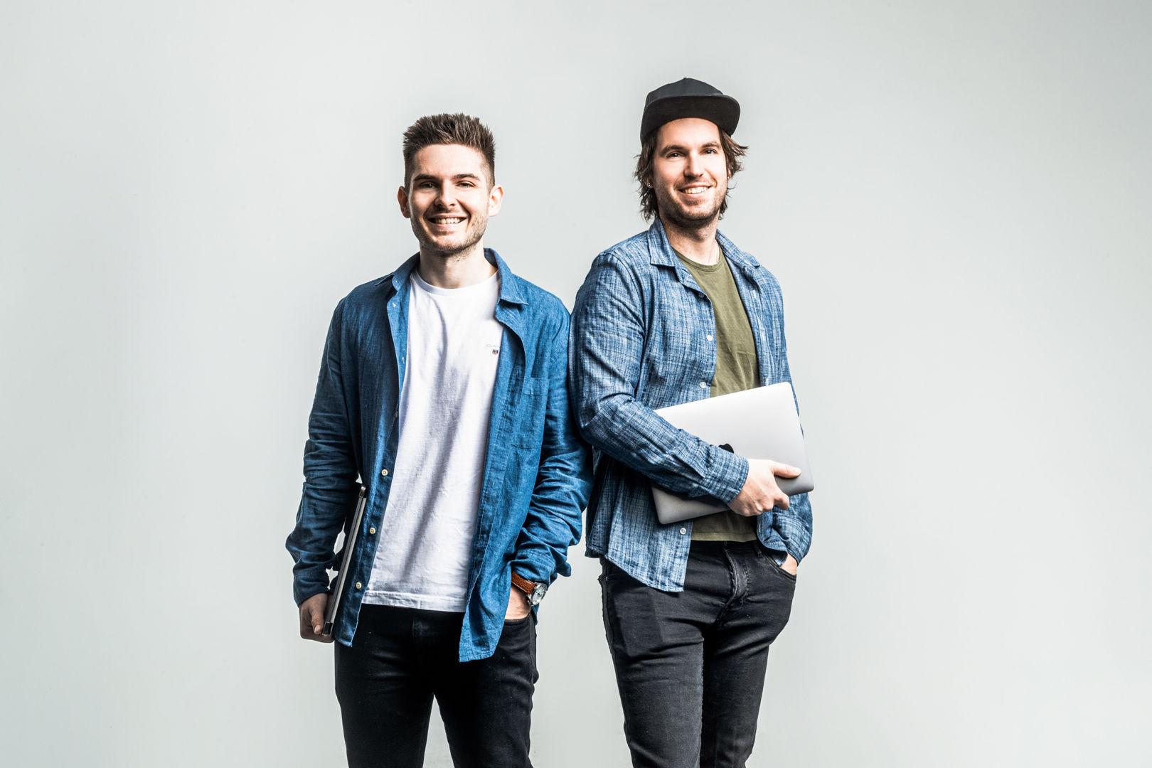 Chris und Dennis Möbus stehen vor einer grauen Wand